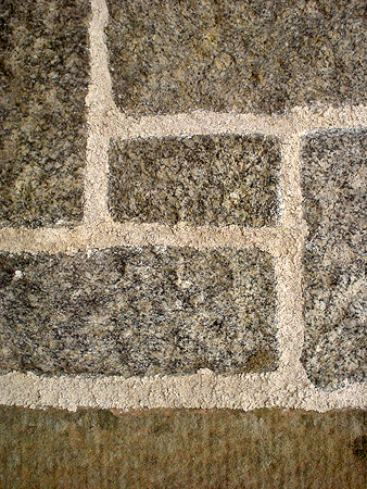 Pointed with open textured finish to squared granite coursed masonry.