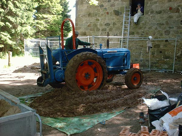 Puddling earth: mechanical help prior to spreading and compacting with a mechanical packer.