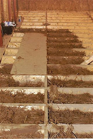 Straw clay floor: filling in grid of pads.