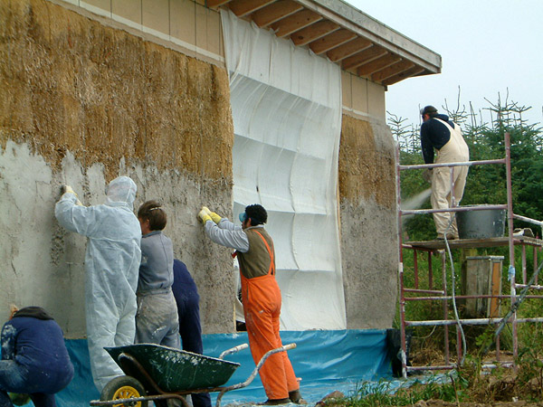 Lime render application: mechanically sprayed and manually pressed into straw substrate.